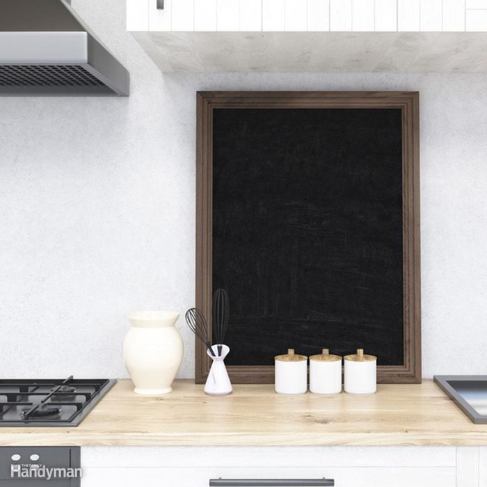 Kitchen counter with blackboard and stove.