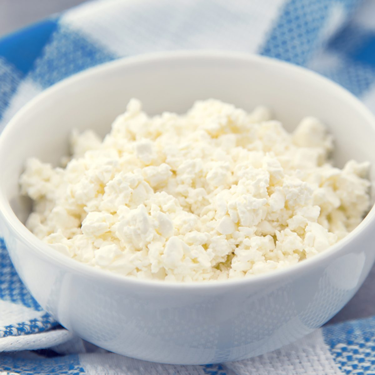 Organic cottage cheese in a white ceramic bowl on the kitchen table. Dairy products for the healthy breakfast.