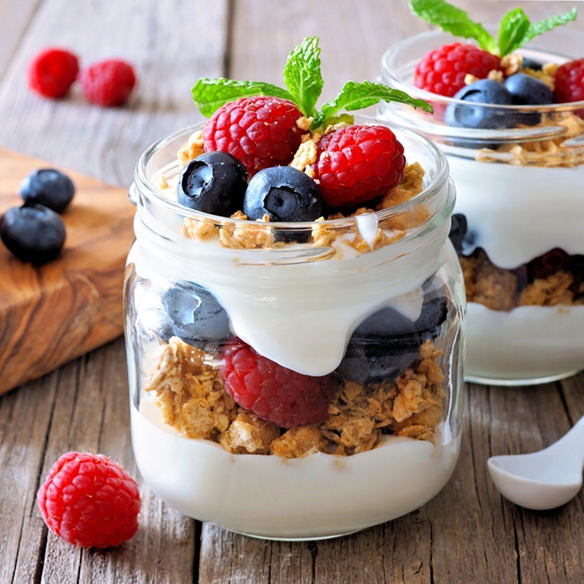 Blueberry and raspberry parfaits in mason jars,