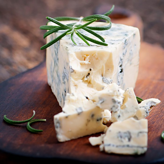 Blue cheese on the old wooden background.