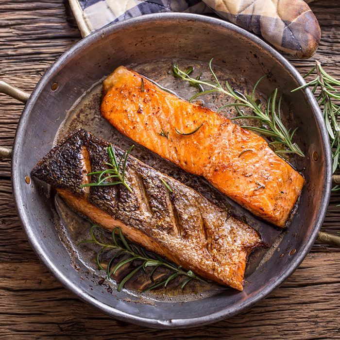 Grilled salmon fillets and herb decoration in old roasted pan.