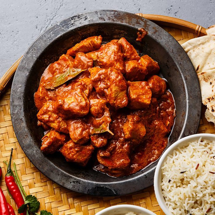 Chicken tikka masala spicy curry meat food in metal plate, rice and naan bread close-up