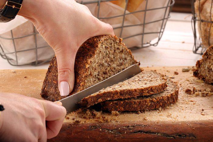 Woman cut whole grain bread on a wooden board
