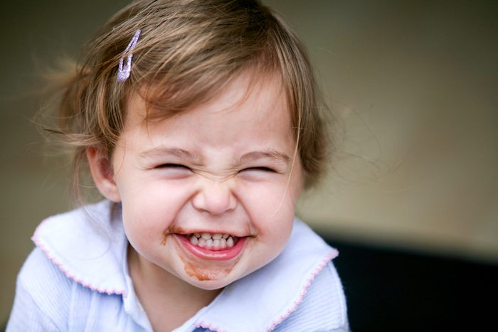 Lovely little girl making funny face after eating chocolate