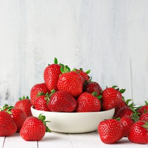 Heap of fresh strawberries in ceramic bowl on rustic white wooden background.
