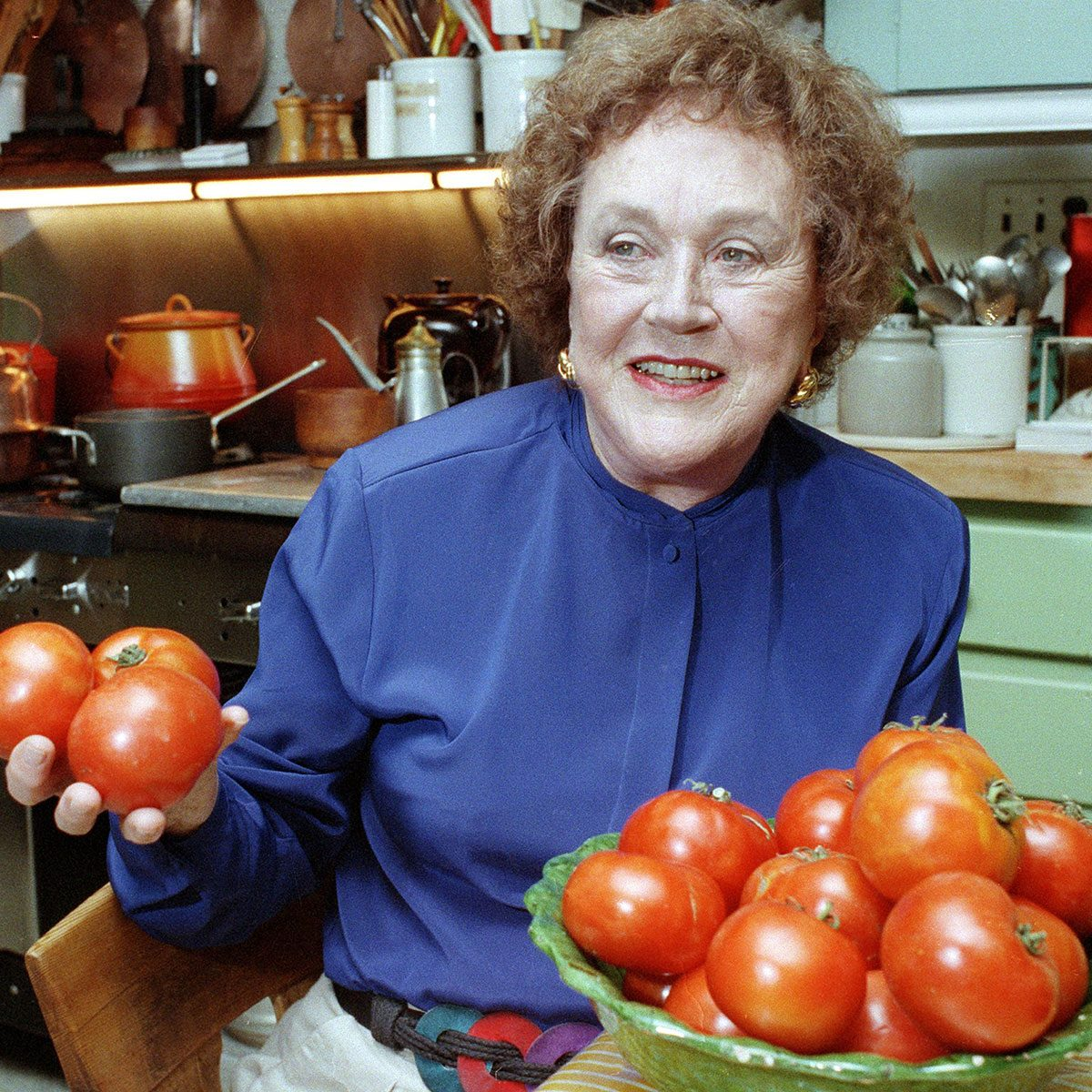 Julia Child holds tomatoes in the kitchen at her home