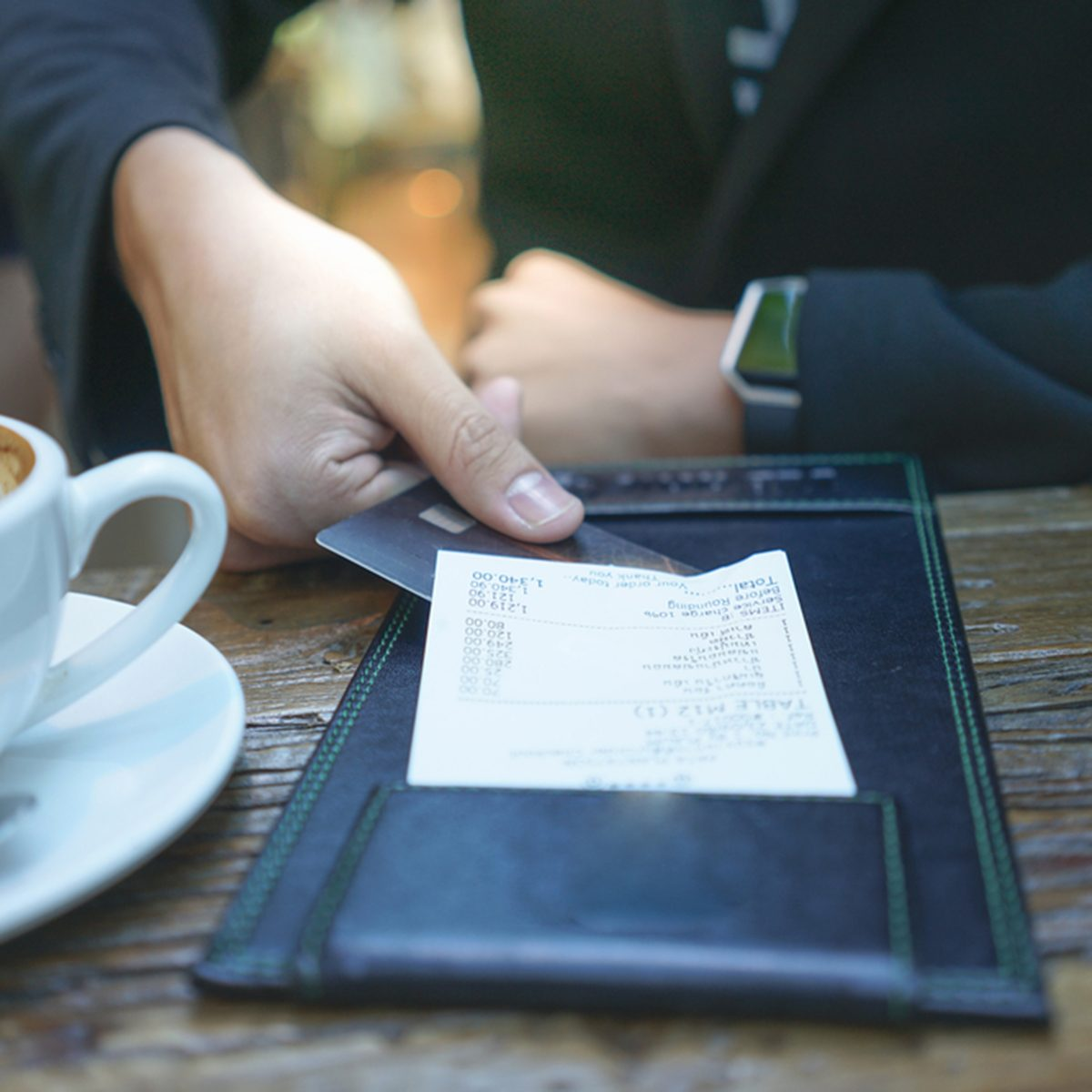 A businessman is paying his bill by credit card at the restaurant.