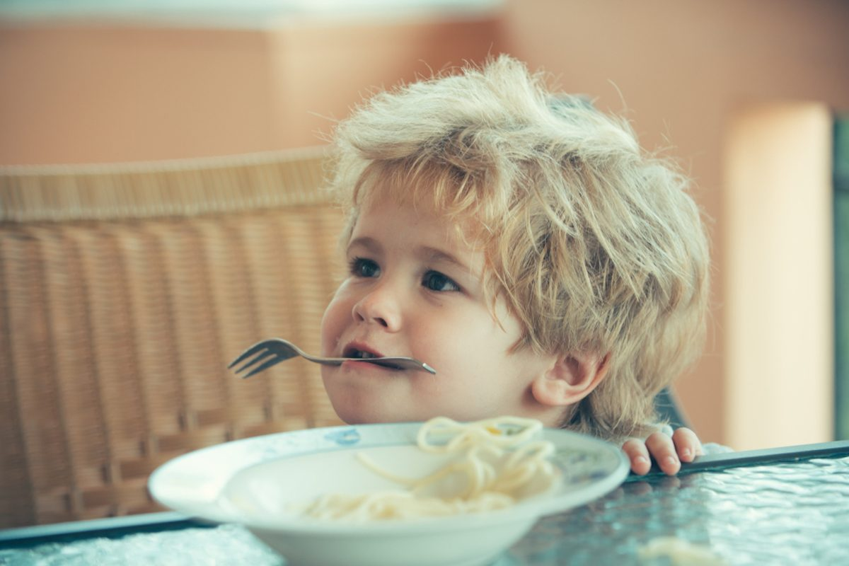 Funny boy holds fork in his teeth. Cheerful kid eats spaghetti in pizzeria. Child spoils with food, baby food as entertainment or play. Plate with food for baby on the table