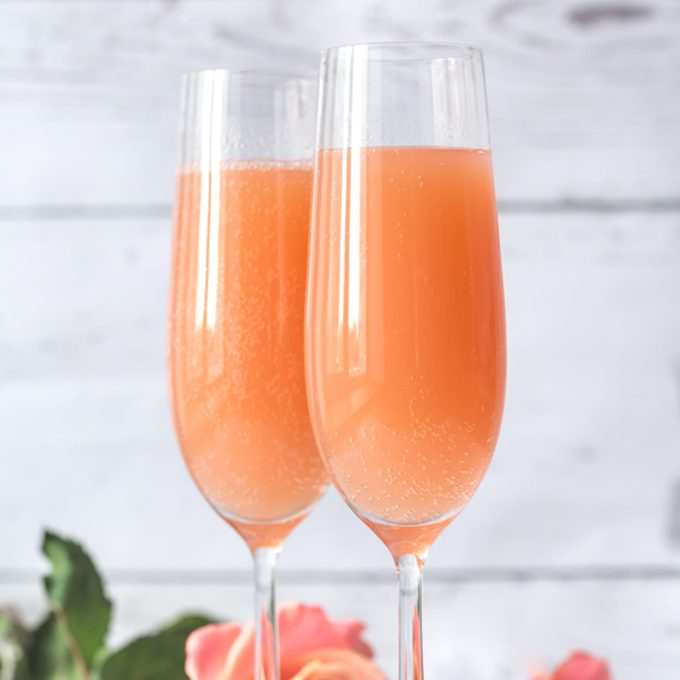 Two glasses of bellini cocktail with bouquet of roses