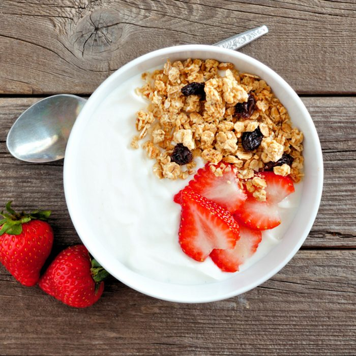 Bowl of yogurt with strawberries and granola over a rustic wood background.