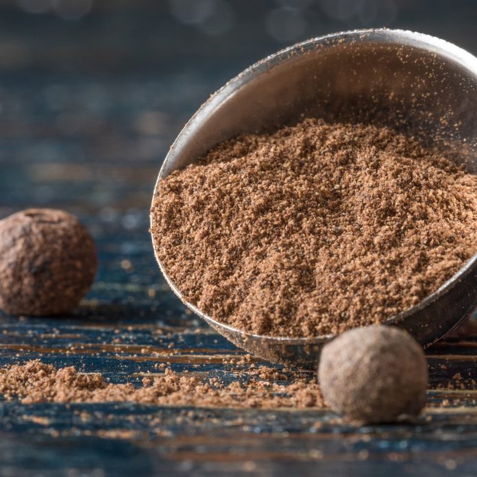 Close-Up Of Ground Allspice In Measuring Spoon Wooden Table