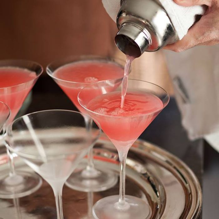 Person pouring drinks into cocktail glasses