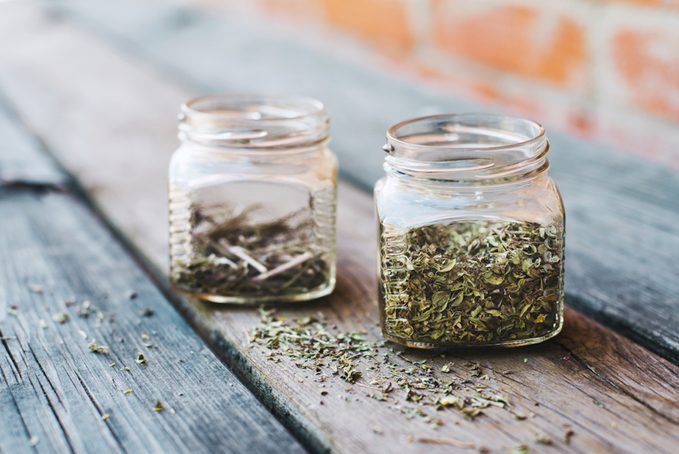 Dried spices in glass jars on wooden table