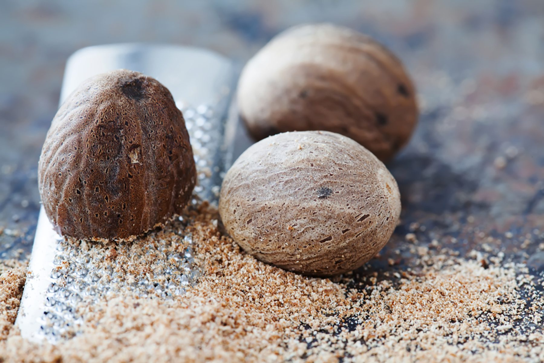 Making nutmeg powder process. Nuts silver grater. Kitchen still life photo. Shallow depth of field, aged brown rusty background. Selective focus.; Shutterstock ID 1059835649