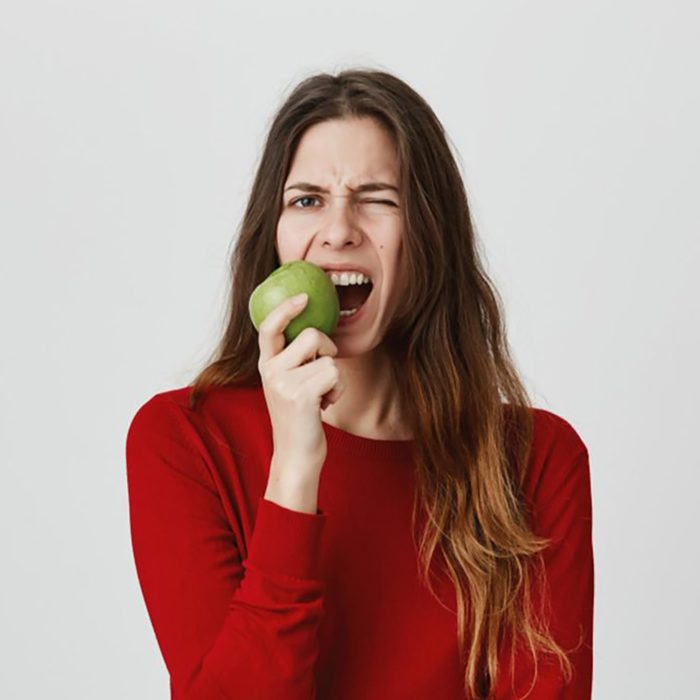 hungry woman in red sweater eating apple