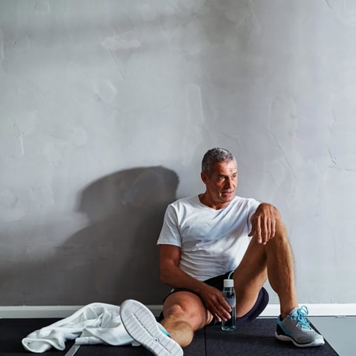older man in workout clothes resting against wall