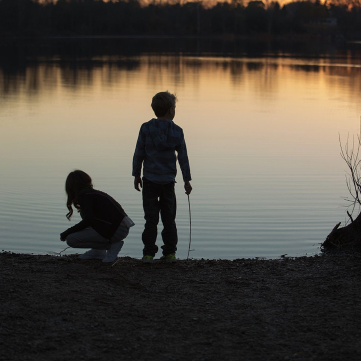 Silhouette of kids playing near the water on sunset