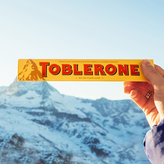Female hand holds Toblerone chocolate on the Matterhorn mountain background in Switzerland.
