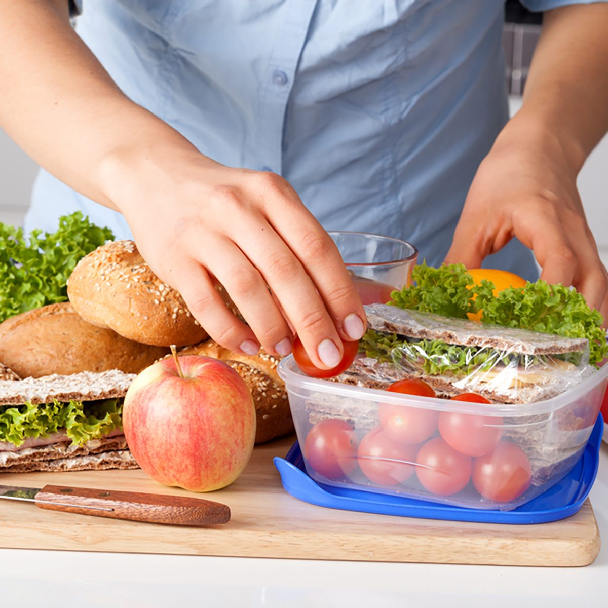 Woman in blue t-shirt preparing a lunchbox in the kitchen