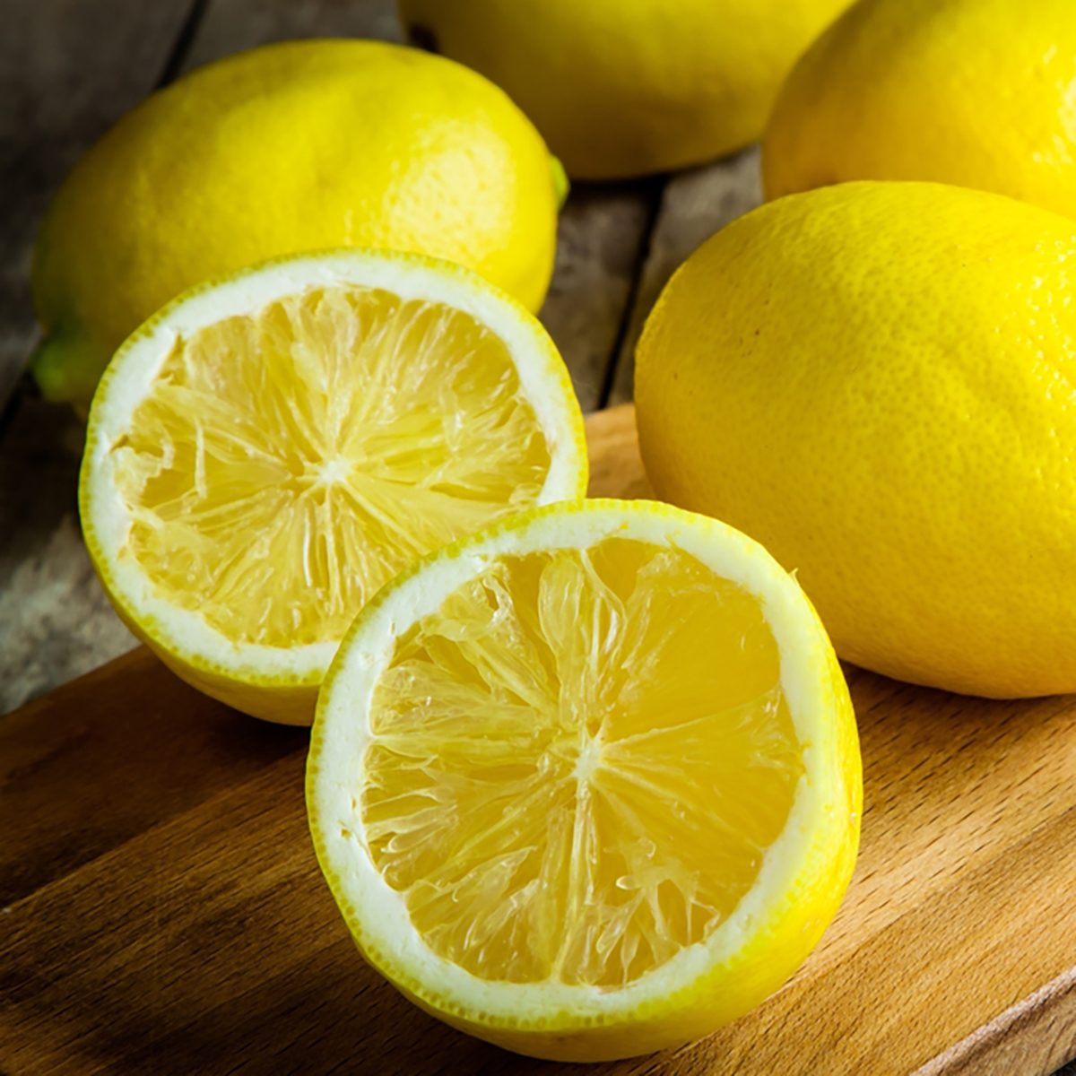 Fresh juicy lemons on a cutting board on a rustic wooden