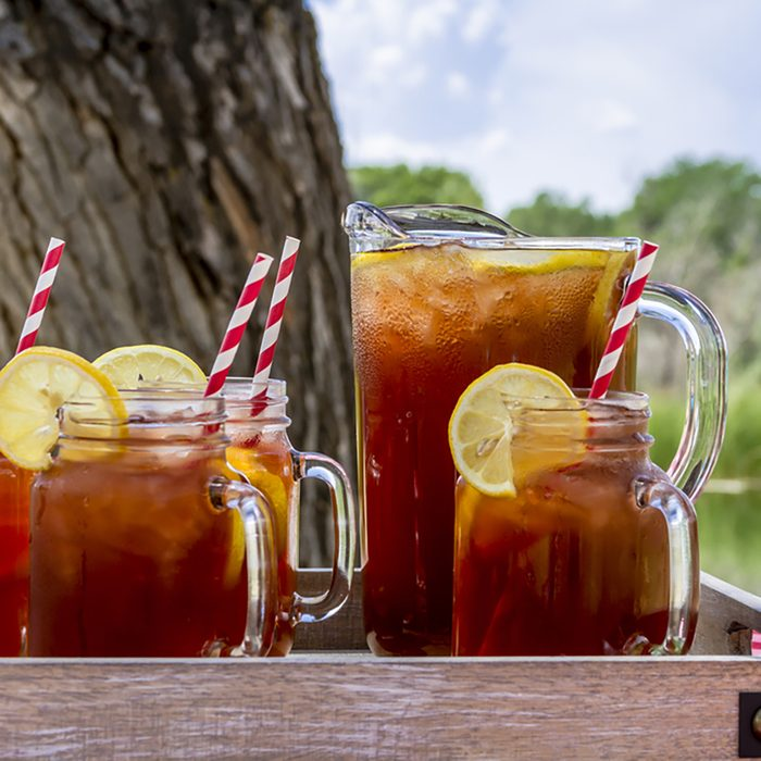 Pitcher and mason jar mugs filled with iced tea and lemons sitting on picnic table with red checked tablecloth