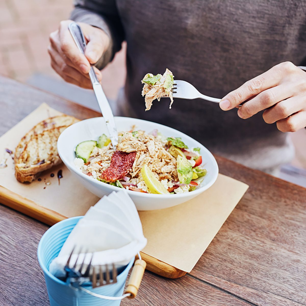 Cropped image of a man on his lunch break eating a fresh and healthy salad with chicken, avocado, sundried tomatoes and fresh sliced baguette on the side while sitting at a wooden table.
