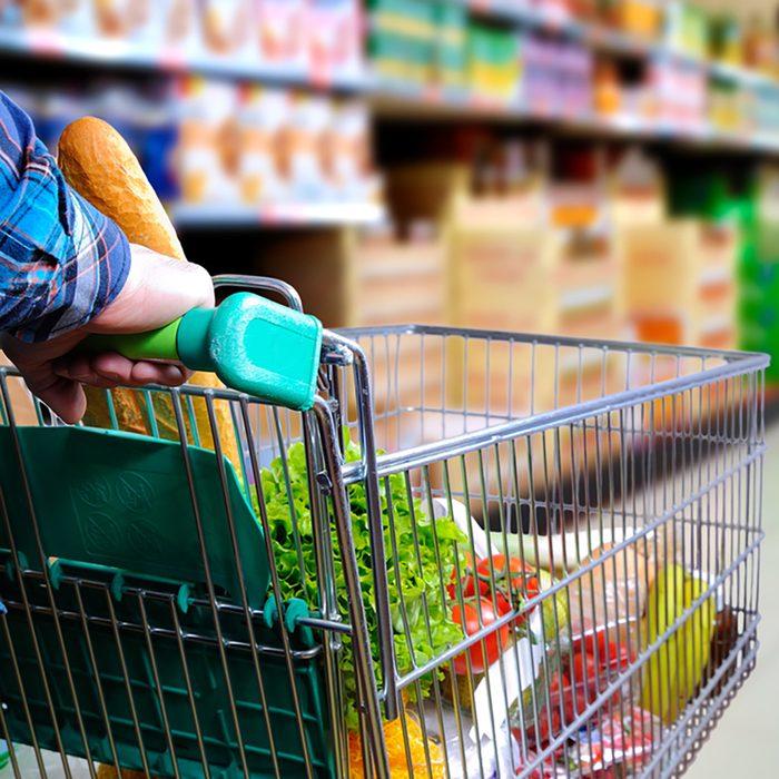 Man pushing shopping cart full of food in the supermarket aisle.