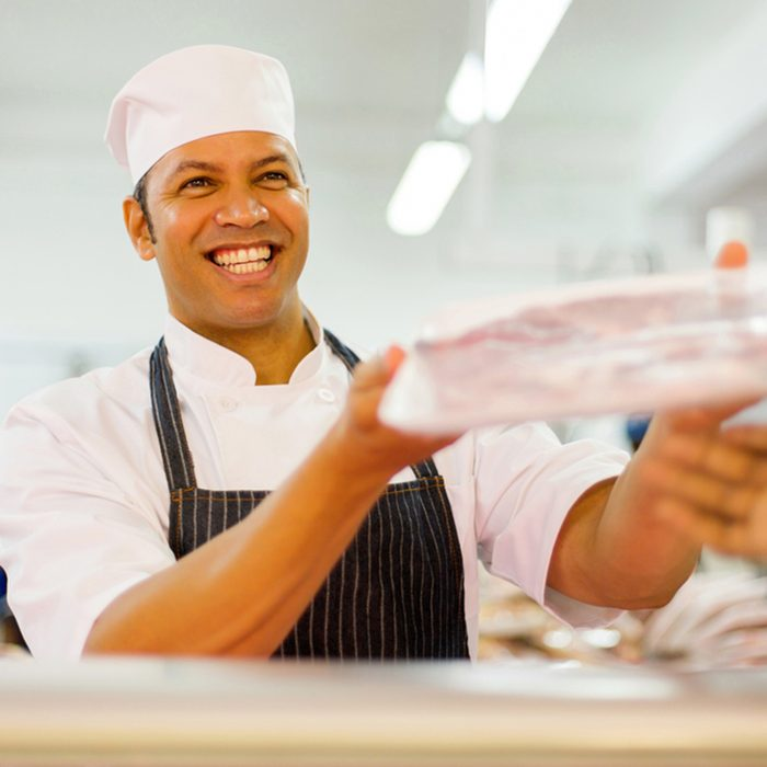 friendly male butcher selling packed meat to customer in butchery
