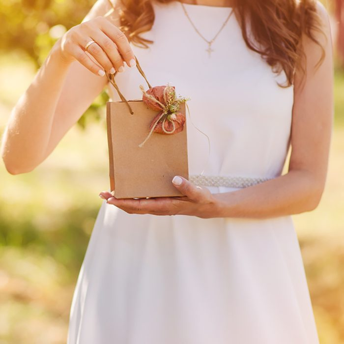 Gift bag with a bow in the hands of women on a wedding anniversary
