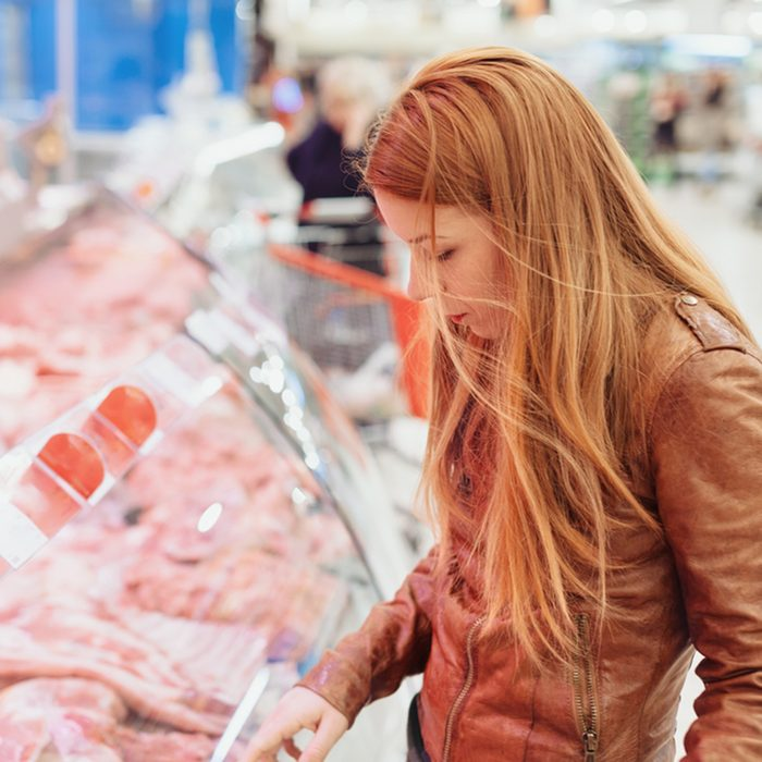 Young woman in butchers shop
