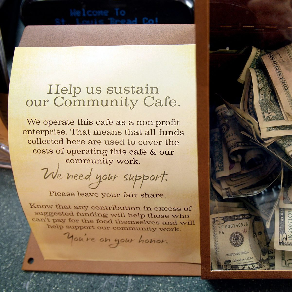 Cash paid for food items sits in a box at the front counter inside a Panera Bread Co. restaurant, in Clayton, Mo.