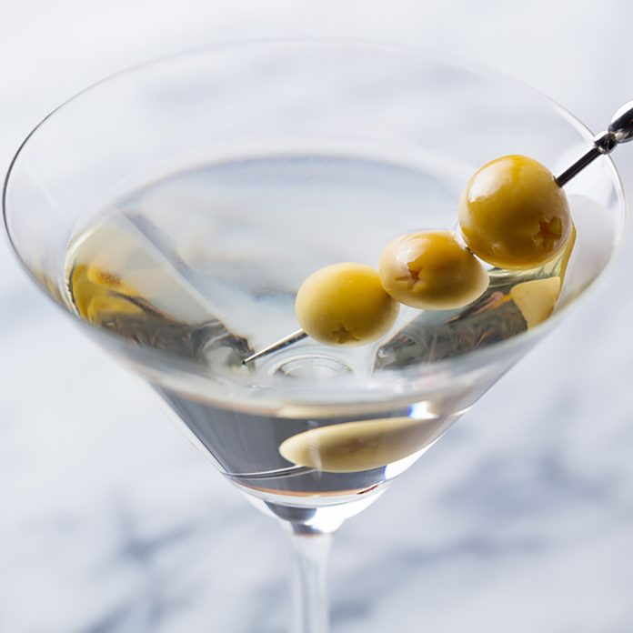 Martini cocktail with green olives on marble board.