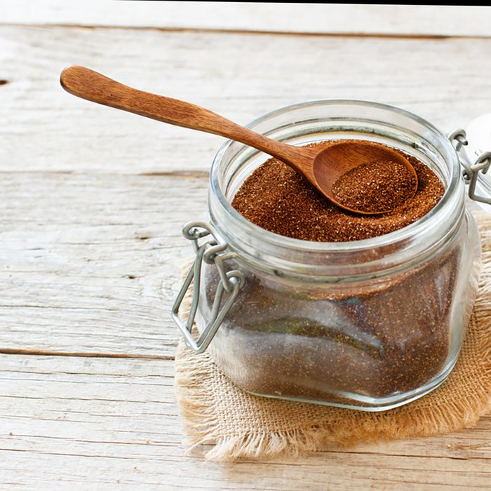 Uncooked teff grain in a glass jar with a spoon