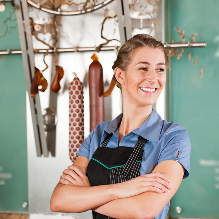 Confident female butcher smiling with arms crossed at butchery
