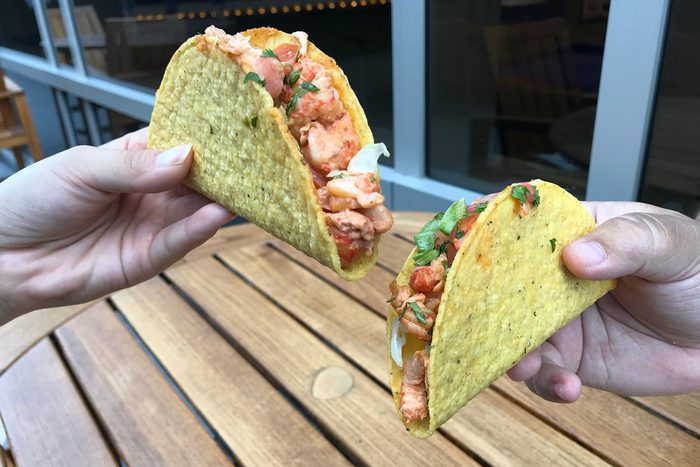 Two hands holding two crayfish tacos from Taco Bell