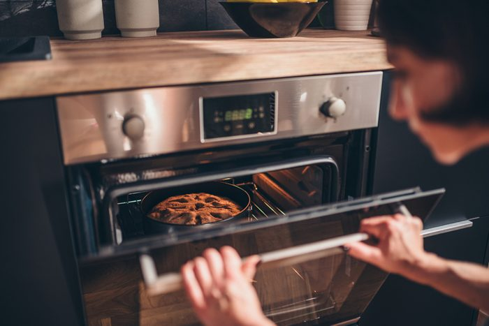 Woman standing by the oven and checking apple pie