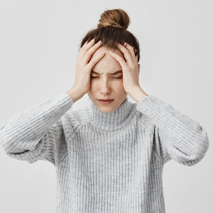 woman holding her head in pain
