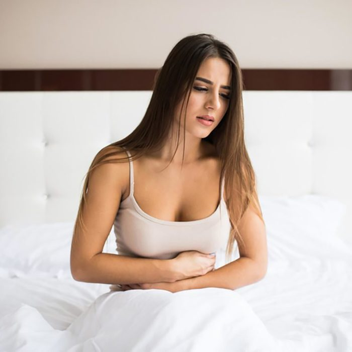 woman holding stomach with cramps