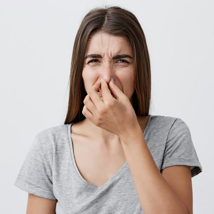 woman pinching her nose from bad smell