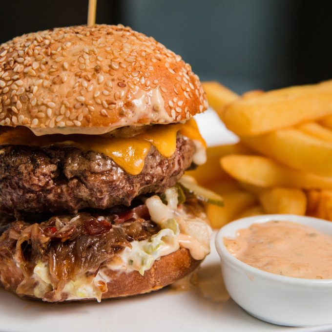 Close up of a tasty burger with sauce and fries