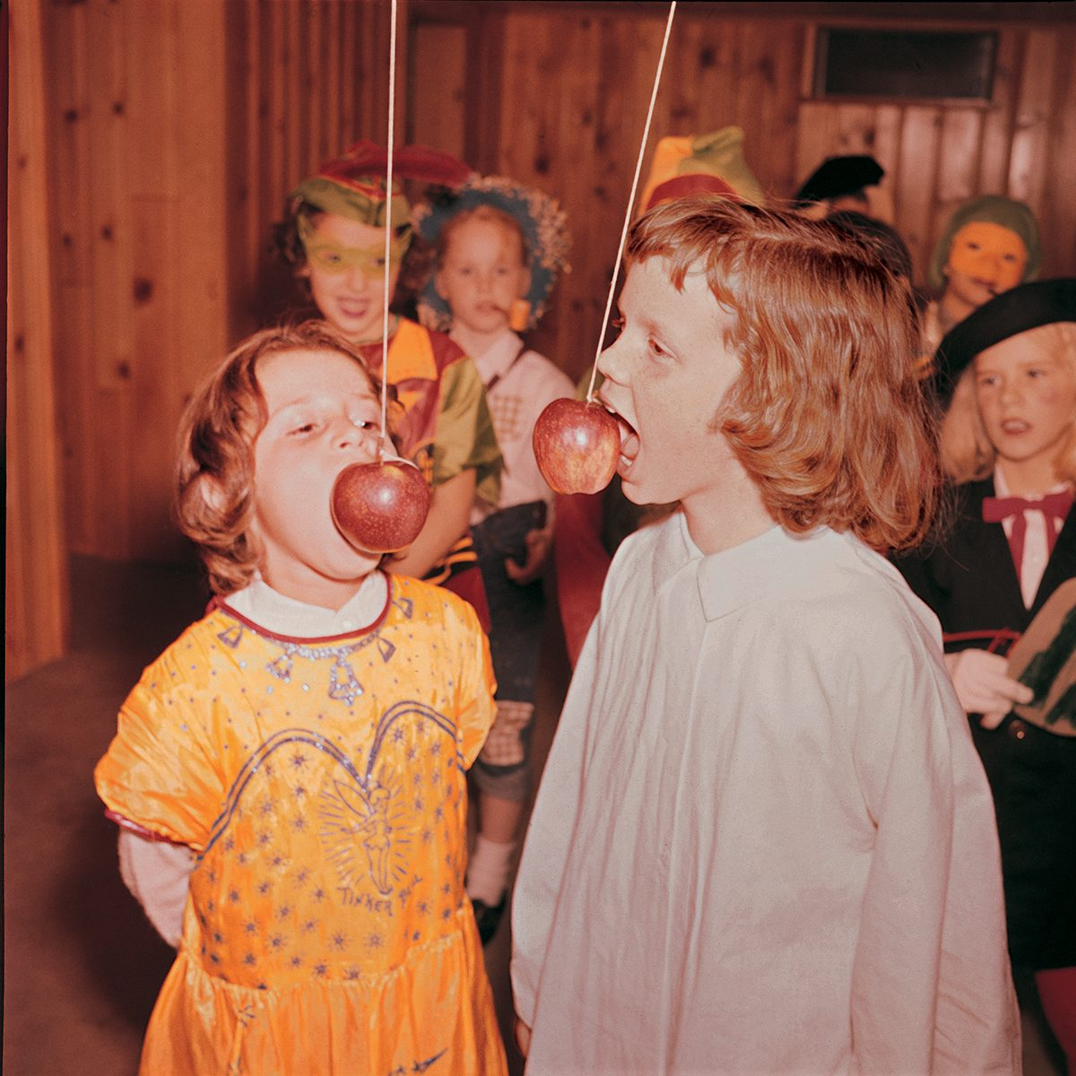 children at a Halloween party eating apples