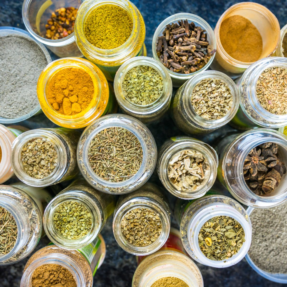 Variety of colorful, different, opened spice jars, from above.