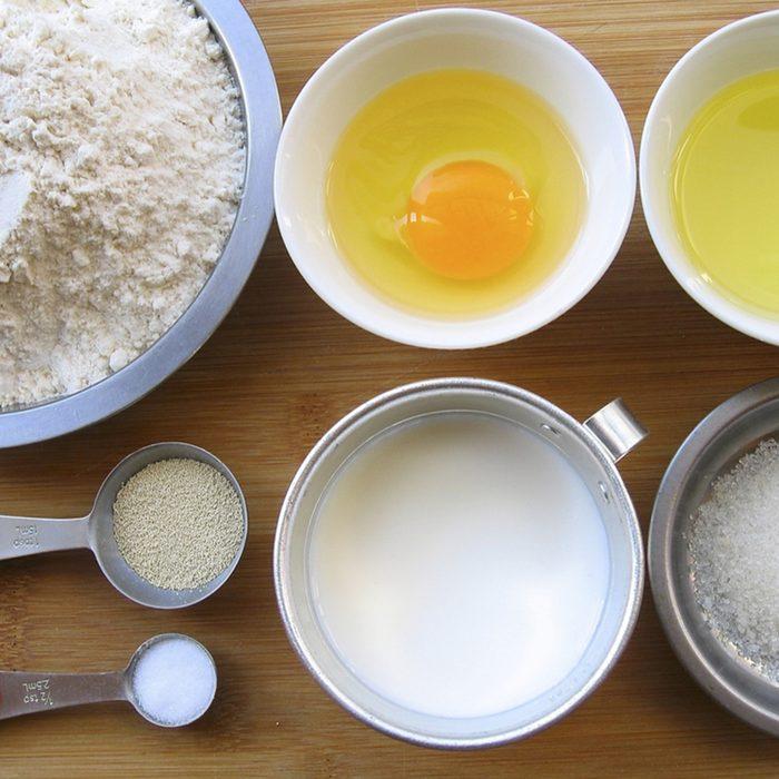 Materials of milk bread -- flour, egg, melted butter, yeast, salt, sugar and milk.