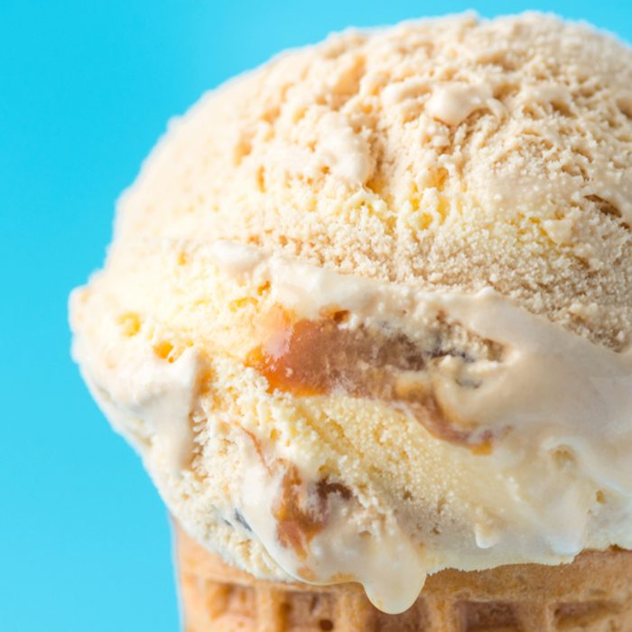 Scoop of Delicious Melting Salted Caramel Toffee Vanilla Ice Cream in Waffle Cone on Blue Background. Summer Sweets Sugar Addiction Indulgence Concept. Recipe Template. Copy Space; Shutterstock ID 1084833002; Job (TFH, TOH, RD, BNB, CWM, CM): Taste of Home