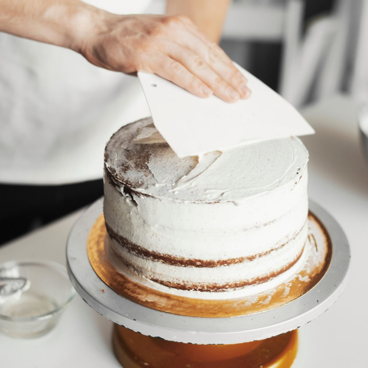Close up of cook smearing butter cream on chocolate cake.; Shutterstock ID 1170976687; Job (TFH, TOH, RD, BNB, CWM, CM): Taste of Home