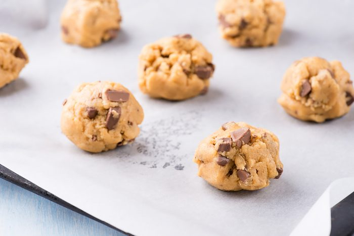 Raw cookie dough on a baking tray with parchment paper
