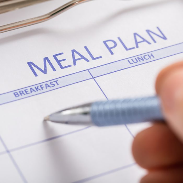 Close-up Of Person Hand Filling Meal Plan Form;