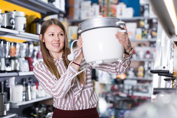 Happy woman choosing slow cooker in household appliances shop