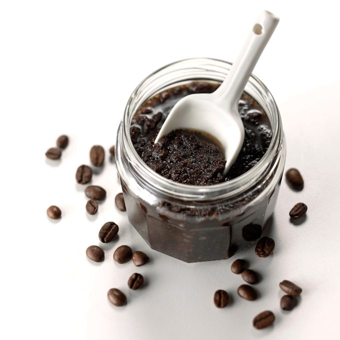 A jar of DIY coffee body scrub with scoop and coffee beans