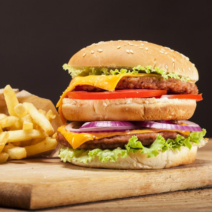 Fresh delicious double burger with cheese, tomato, onion, french fries and lettuce on wooden table and brown background